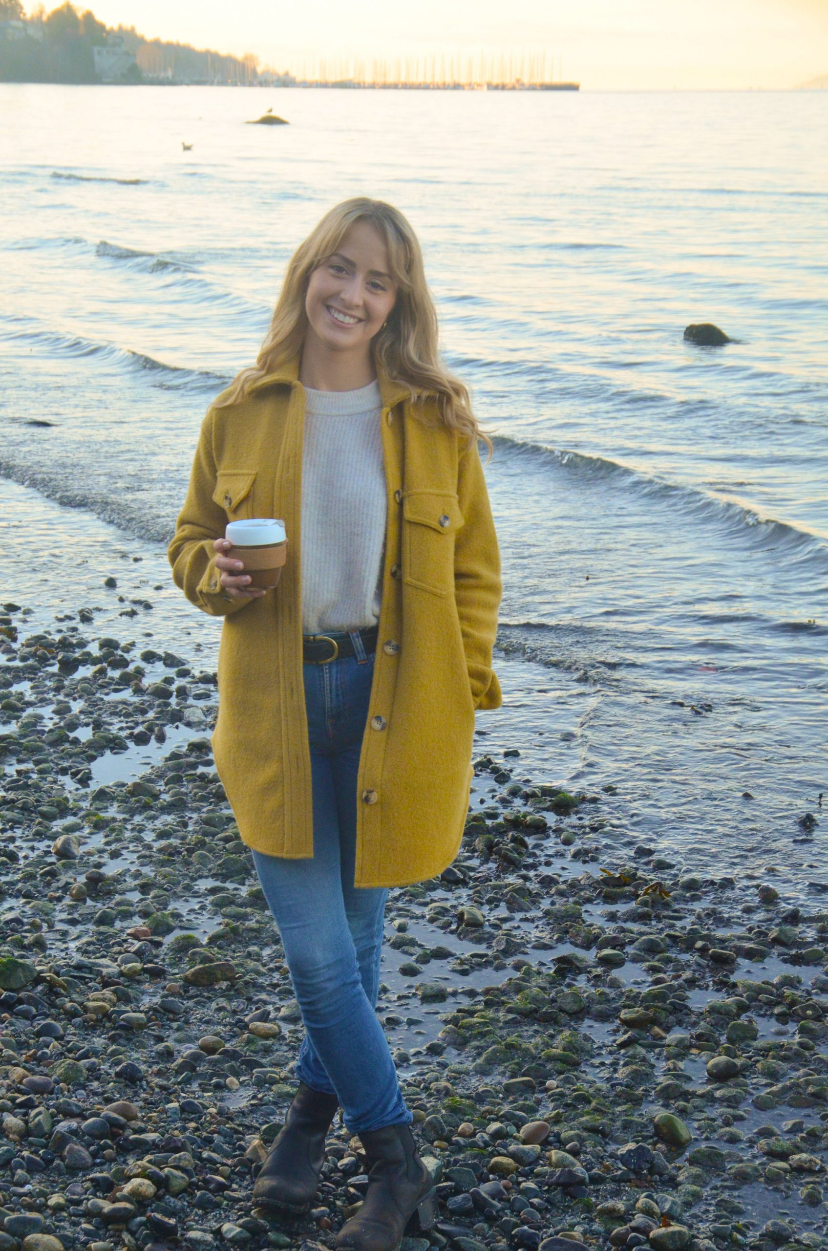 Photo of fleck founder Jazmin Welch in a yellow overcoat with sunshine coming behind her blond hair.