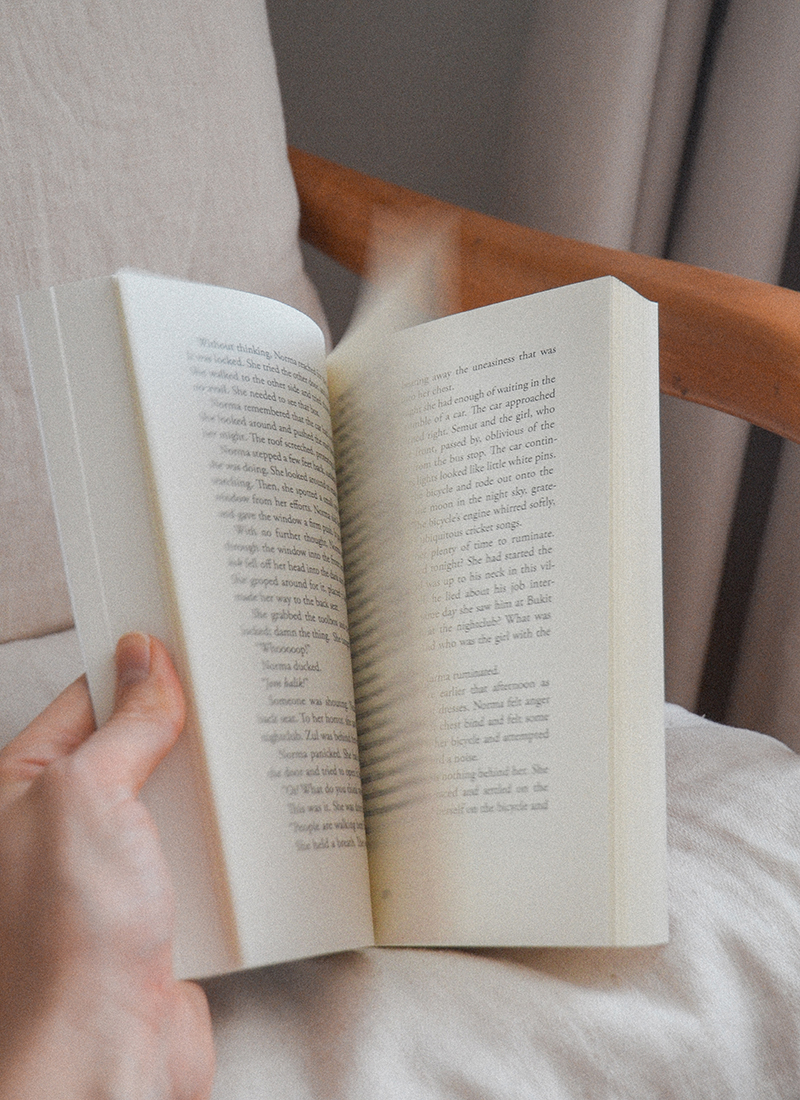 Photo of a book getting flipped, the pages are blurred, the book is held in someones left hand and is resting on a chair
