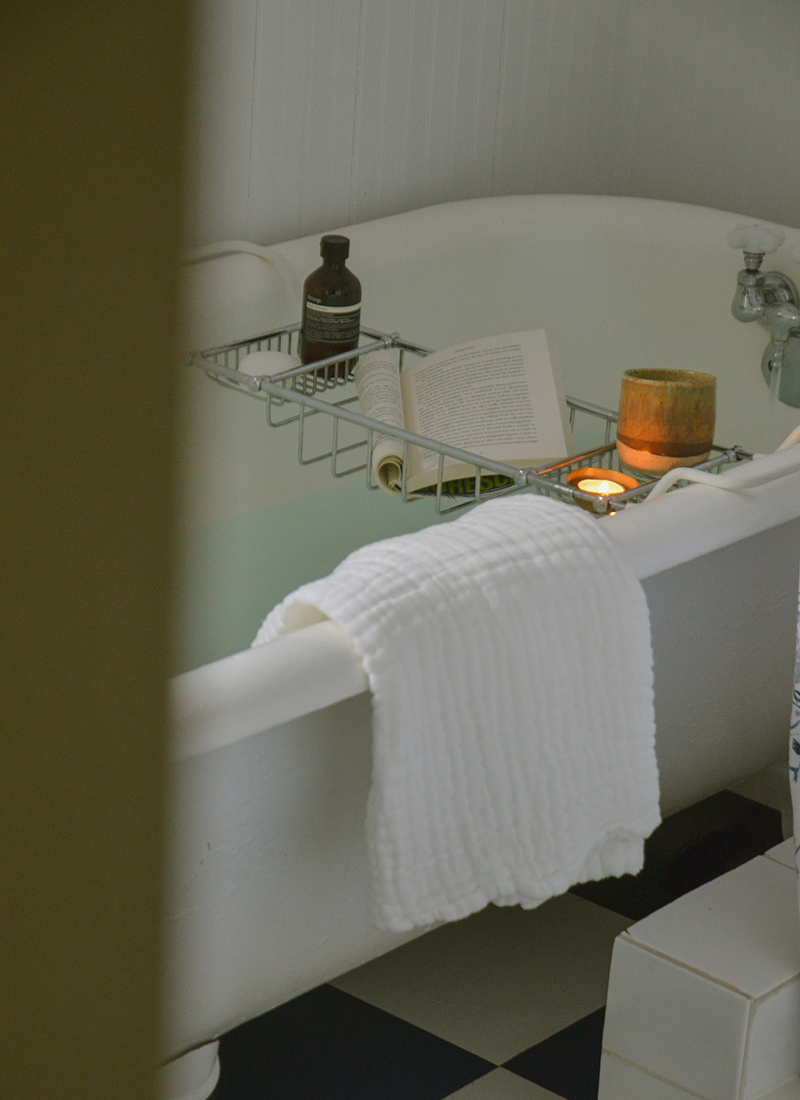 Photo peaking into a bathroom with a claw tub, with a bath drawn, a candle and a book in a tub caddie with a white towel hanging on the edge