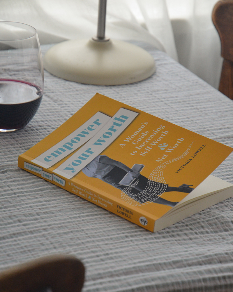 Book cover design for Empower Your Worth by Victoria Lowell. The book is sitting on a table beside a glass of red wine